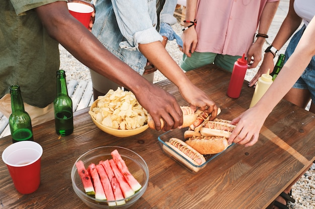 Group of intercultural friends taking fresh grilled hotdogs