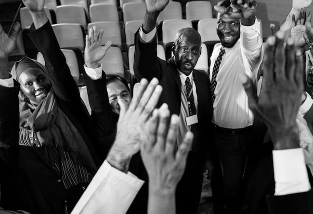 Gruppo di uomini d'affari internazionali che solleva le mani