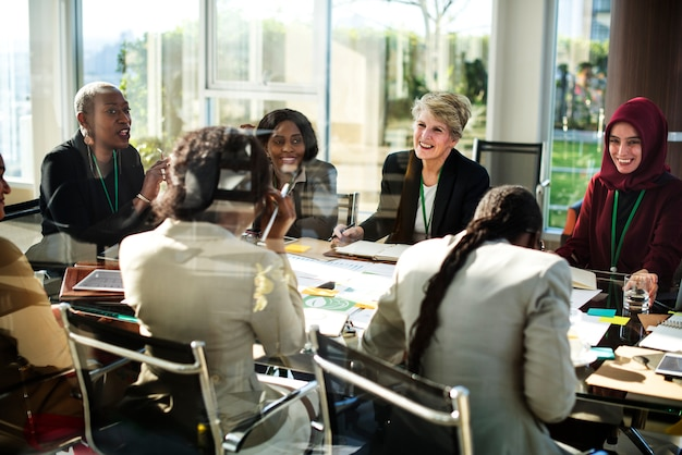 A group of international business women are laughing in a meeting