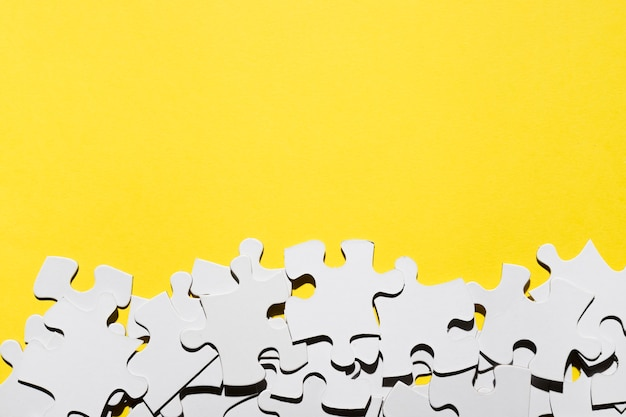 Group of jigsaw puzzle pieces at the bottom of yellow backdrop