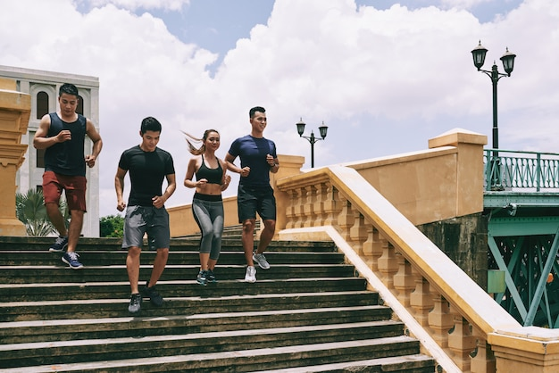 A group of joggers running down the stairs on a sunny summer day