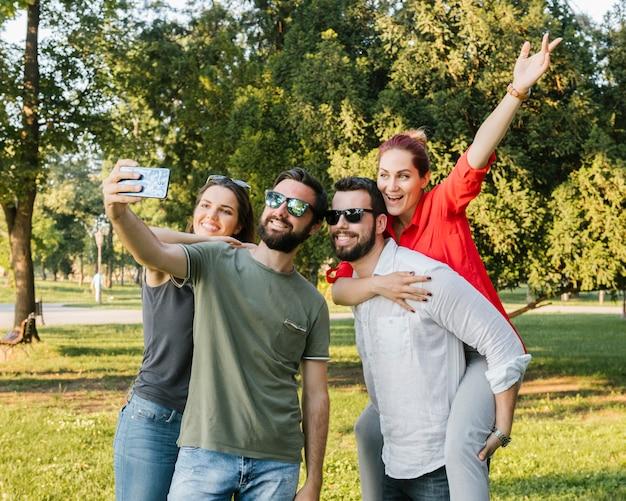 Group of joyful adult friends taking selfie together