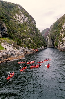 Group kayaking in river canyon in knysna, south africa