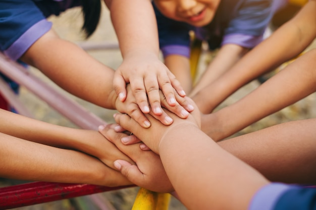 Group of kids hands of together joining for teamwork.