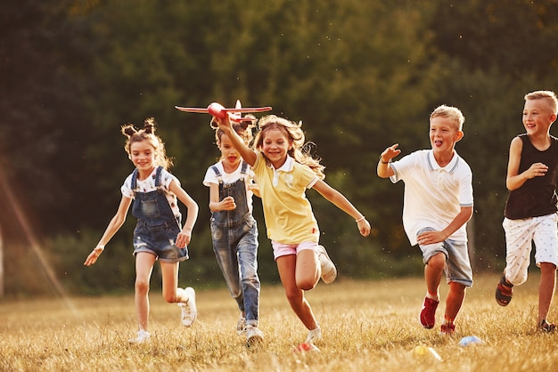 Group of kids having fun outdoors with red toy airplane in hands.