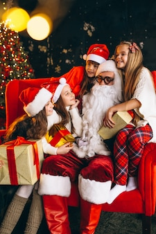 Group of kids sitting with santa and presents on christmas eve