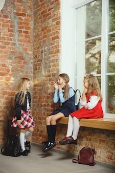 Gruppo di bambini che trascorrono del tempo insieme dopo la scuola. amici belli che riposano dopo le lezioni prima di iniziare a fare i compiti. interno loft moderno. scuola, amicizia, educazione, concetto di solidarietà.