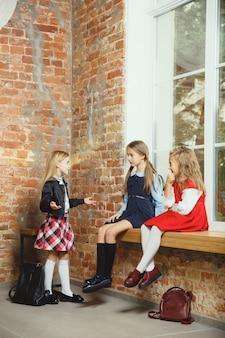 Gruppo di bambini che trascorrono del tempo insieme dopo la scuola. amici belli che riposano dopo le lezioni prima di iniziare a fare i compiti