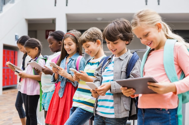 Group of kids using mobile phone and digital tablet