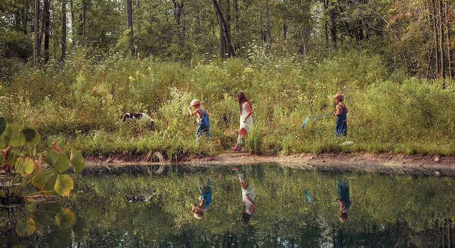 Group of kids walking through a field covered in greenery and reflecting on the lake under sunlight