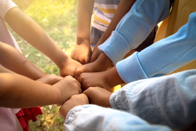 Group of kids with building kit making fist bump at school