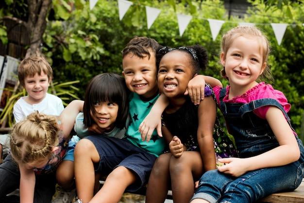 Group of kindergarten kids friends arm around sitting and smiling fun