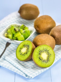 Group of kiwi fruit (cut up and whole) on the wooden table