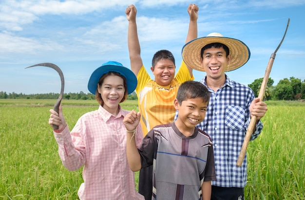 Group of laugh happy asian farmer man, woman and two kids smile and holding tools at green rice field
