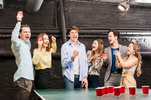 Group of laughing friends enjoying beer pong on table
