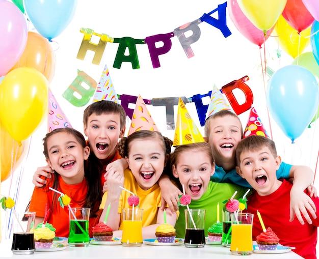 Gruppo di bambini che ridono divertendosi alla festa di compleanno - isolato su un bianco.