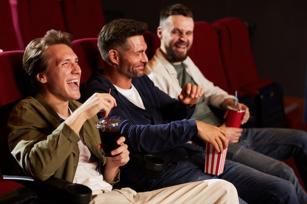 Group of laughing male friends watching comedy movie in cinema and eating popcorn while sitting in row on red seats, copy space