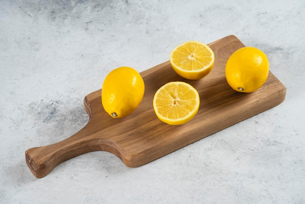 Group of lemon fruits on a wooden board .