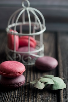 Group of macarons made of strawberries, cream, chocolate and blueberries. rustic photo.