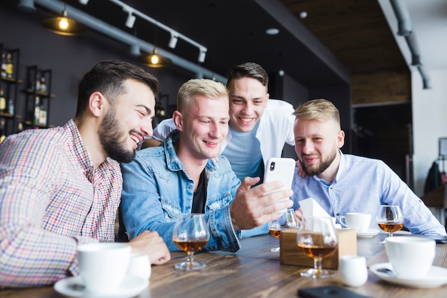 Group of male friends looking at smartphone sitting at restaurant with drinks on table