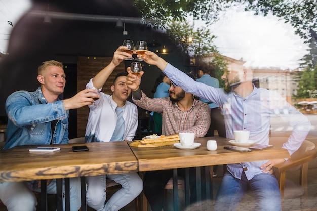 Gruppo di amici maschi che alza pane tostato nel ristorante