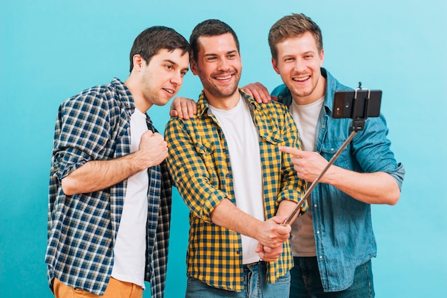 Group of male friends taking selfie on mobile phone against blue backdrop