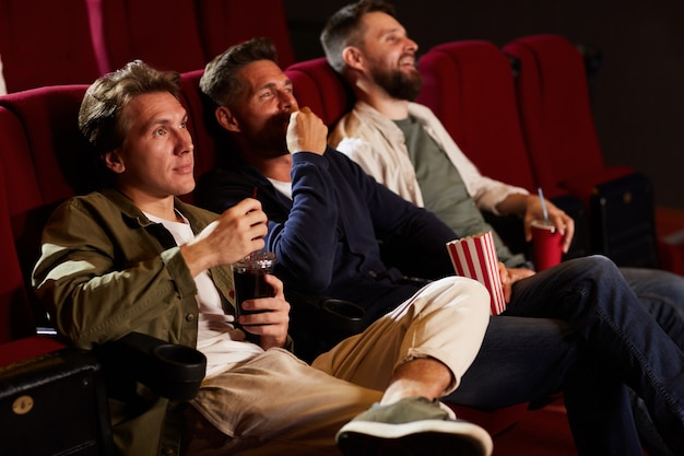 Group of male friends watching movie in cinema theater and eating popcorn while sitting in row on red seats, copy space