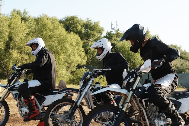 Group of male motorcyclists in helmets being at starting line while preparing for race