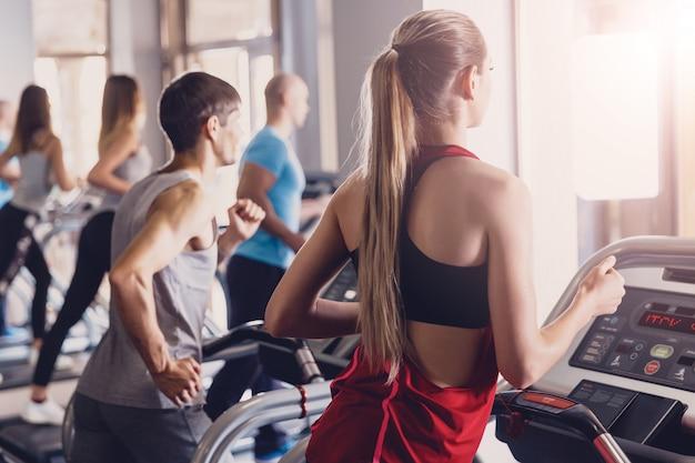 Группа мужчины и девушки выполняют упражнения на беговой дорожке