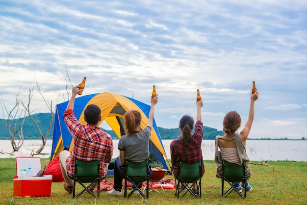 Group of man and woman enjoy camping picnic and barbecue at lake with tents in background. young mixed race asian woman and man.