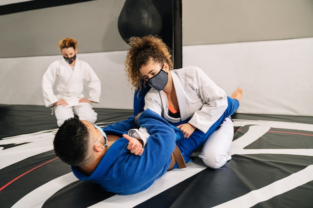Group of martial arts and judo with kimonos on the gym floor mat with a student watching all of them wearing a mask because of the covid 19