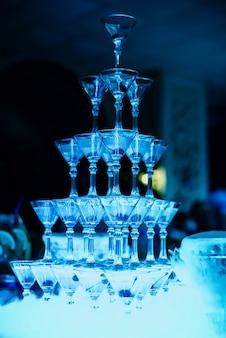 Group of martini glasses with bright blue illumination