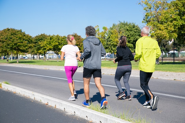 Group of mature joggers in sports clothes running outside, training for marathon, enjoying morning workout. full length shot. retired people and active lifestyle concept
