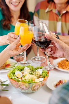 Group of mature people drinking juice at dinner at home