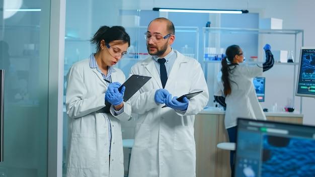 Gruppo di ricercatori medici che discutono sullo sviluppo del vaccino in piedi in un laboratorio attrezzato puntando sul tablet e prendendo appunti