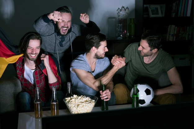 Group of men drinking beer and watching soccer on tv