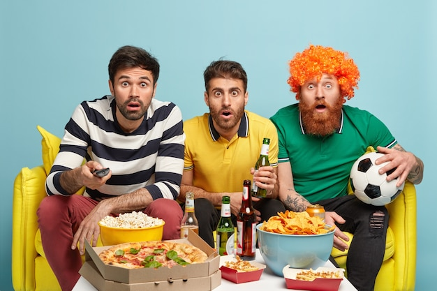 Group of men football fans watch with great surprise final match, shocked by favorite team loose, hold remote control and ball, stare at tv, drink cold beer, eat pizza, pose on yellow sofa.