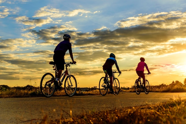 Group of men ride bike at sunset .