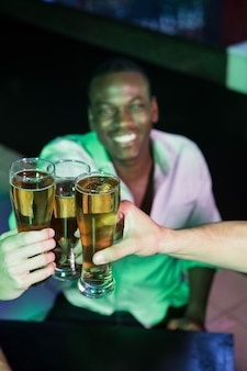 Group of men toasting with glass of beer in bar