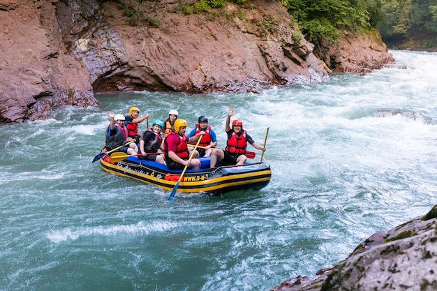 Group of men and women are rafting on the river, extreme and fun sport