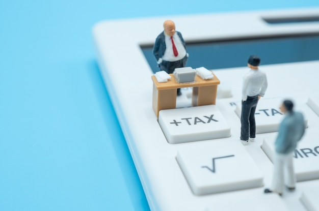 A group of miniature businessmen stand on calculator tax button, consider impact of covid-19 outbreak to economic, finance, income and tax.