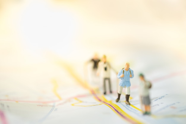 Group of miniature figures stand and walking on map.