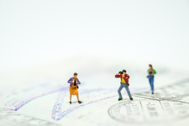 Group of miniature mini figures with camera taking photo and standing on passport with stamps