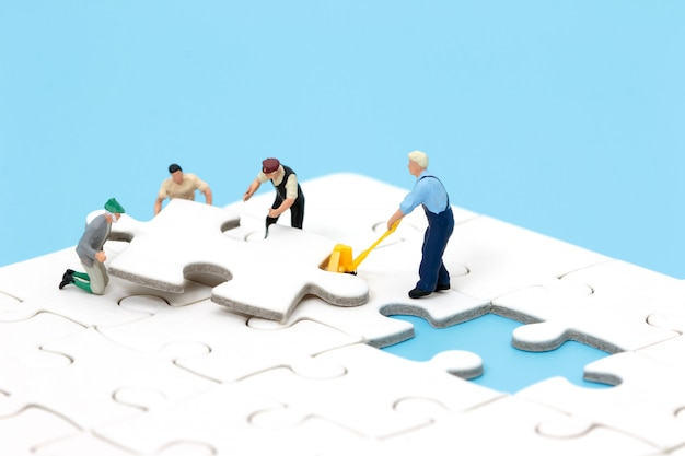 Group of miniature people assembling jigsaw puzzle. business teamwork concept.