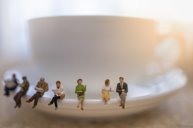 Group of miniature people figures sitting, talking, waiting and reading newspaper and book on white plate