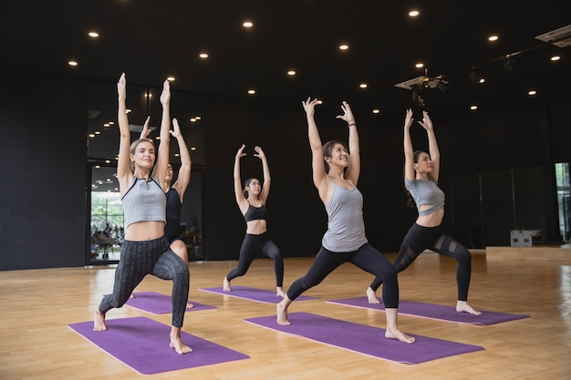 Group of mix race of caucasian and asian people both women and men practicing yoga pose at studio gym