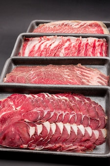 Group of mix raw beef. sliced raw beef place in a row on a black plastic tray isolated on a black background. sliced meat for cooking, fresh meat for grilling, yakiniku, sukiyaki or shabu.