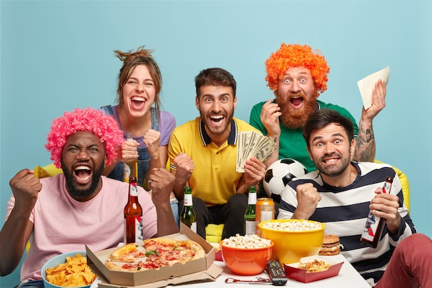 Group of mixed race best friends watch football match with excitement, shout for favorite team, make sport betting on money, clench fists, eat pizza, popcorn, drink beer, celebrate goal, cheer up