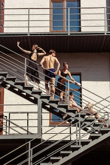 Il gruppo di ballerini moderni che si esibiscono sulle scale della città