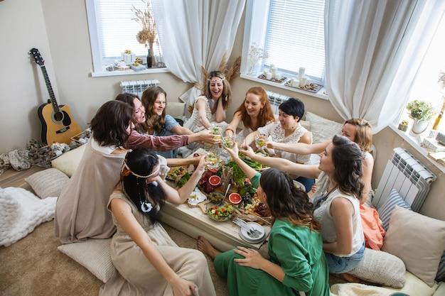 Группа современных хиппи подруг празднуют праздник за столом, где подают здоровую пищу